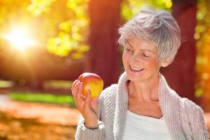 Smiling woman with dentures in Farmington holding an apple
