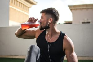 Man drinking sports drink while working out